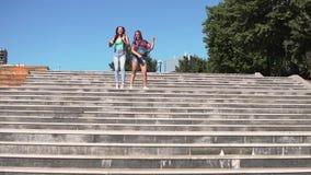 Δύο φίλες κοριτσιών είναι ευτυχής και πηδώντας στάση στα βήματα στην οδό φιλμ μικρού μήκους