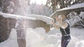 Δύο φίλες κοριτσιών που γύρω στο χιόνι, που έχει το χιόνι ρίψης διασκέδασης στον αέρα και απόλαυση του χειμερινού πρωινού απόθεμα βίντεο