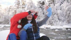 Δύο φίλες κοριτσιών το χειμώνα κοντά στη συνεδρίαση ποταμών βουνών σε έναν βράχο και μια συζήτηση που χρησιμοποιούν την τηλεοπτικ απόθεμα βίντεο