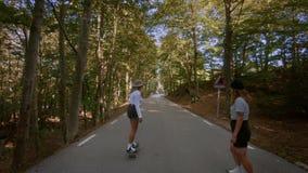 Δύο φίλες οδηγούν skateboard longboard στο δρόμο φιλμ μικρού μήκους