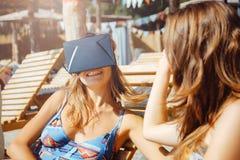 Δύο φίλες που έχουν τη διασκέδαση με τα γυαλιά VR και το smartphone στην παραλία στοκ φωτογραφίες