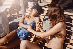 Δύο φίλες που έχουν τη διασκέδαση με τα γυαλιά VR και το smartphone στην παραλία στοκ εικόνες