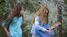 Δύο φίλες που έχουν τη διασκέδαση υπαίθρια Οι νέοι που απολαμβάνουν μια ημέρα άνοιξη στα δασικά μικρά κορίτσια που παίζουν την κι φιλμ μικρού μήκους