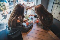 Δύο φίλες που μιλούν στον καφέ ενώ ποτό ένα τσάι συνεδρίαση στοκ φωτογραφία με δικαίωμα ελεύθερης χρήσης