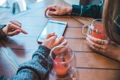 Δύο φίλες που μιλούν στον καφέ ενώ ποτό ένα τσάι συνεδρίαση στοκ εικόνες