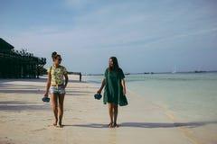 Δύο φίλες που περπατούν την ωκεάνια ακτή το πρωί στοκ φωτογραφίες