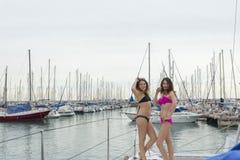 Δύο φίλες που χαλαρώνουν σε ένα γιοτ σε ένα λιμάνι στοκ φωτογραφίες