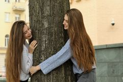 Δύο φίλοι γύρω, κοιτάζοντας έξω από πίσω από ένα δέντρο Στοκ εικόνα με δικαίωμα ελεύθερης χρήσης