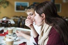 Δύο φίλοι επικοινωνούν με τα τρόφιμα, πίνουν τον καφέ και τρώνε το κέικ Στοκ εικόνα με δικαίωμα ελεύθερης χρήσης