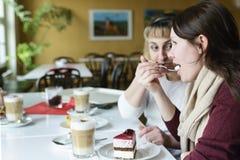 Δύο φίλοι επικοινωνούν με τα τρόφιμα, πίνουν τον καφέ και τρώνε το κέικ Στοκ φωτογραφία με δικαίωμα ελεύθερης χρήσης