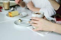 Δύο φίλοι επικοινωνούν με τα τρόφιμα, πίνουν τον καφέ και τρώνε το κέικ Στοκ Εικόνες