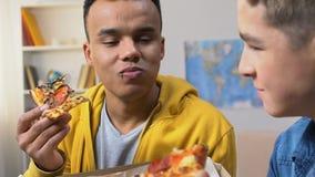 Δύο φίλοι κολλεγίων που απολαμβάνουν τις φρέσκες φέτες πιτσών, υψηλή ελεύθερη παράδοση γεύματος θερμίδας απόθεμα βίντεο