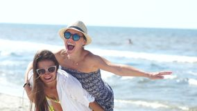 Δύο φίλοι κοριτσιών έχουν τη διασκέδαση στην παραλία Καλοκαιρινές διακοπές, γυαλιά ηλίου, ένα καπέλο αχύρου, που γύρω φιλμ μικρού μήκους