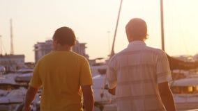 Δύο φίλοι περπατούν στον περίπατο Όμορφο χρυσό ηλιοβασίλεμα στην επίδραση παραλιών και φακών γιοτ flarre αργός φιλμ μικρού μήκους