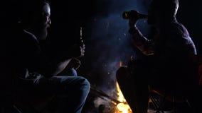 Δύο φίλοι που κάθονται ανοίγουν πυρ τη νύχτα και μπύρα κατανάλωσης, χαλαρώνοντας το χρόνο απόθεμα βίντεο
