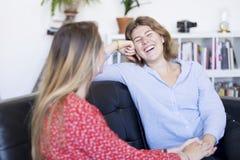 Δύο φίλοι που μιλούν και που γελούν σε έναν καναπέ στο καθιστικό στοκ εικόνες