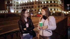Δύο φίλοι που πίνουν τον καφέ και που μιλούν στην πόλη νύχτας απόθεμα βίντεο