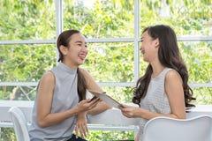 Δύο φίλοι που ψωνίζουν on-line με την πίστωση Όμορφες νέες γυναίκες που χρησιμοποιούν το ψηφιακές κινητές τηλέφωνο και την ταμπλέ στοκ φωτογραφία
