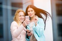 Δύο φίλες που εξετάζουν το τηλέφωνο στοκ εικόνες με δικαίωμα ελεύθερης χρήσης