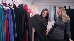 Δύο φίλες στον περίπατο αγορών στο εμπορικό κέντρο με τις τσάντες και επιλογή του φορέματος απόθεμα βίντεο