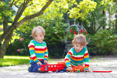 Δύο φίλοι αγοριών που παίζουν με το κόκκινο σχολικό λεωφορείο Στοκ εικόνες με δικαίωμα ελεύθερης χρήσης