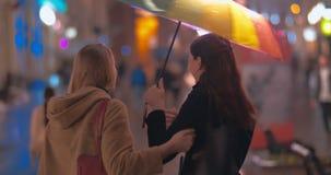 Δύο φίλοι γυναικών που συναντιούνται το βροχερό βράδυ απόθεμα βίντεο