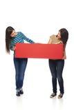 Δύο φίλοι κοριτσιών με το κόκκινο έμβλημα Στοκ φωτογραφία με δικαίωμα ελεύθερης χρήσης