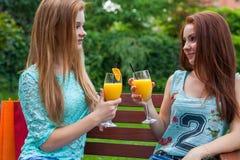 Δύο φίλοι πίνουν την αναζωογόνηση, κρύος χυμός από πορτοκάλι Στοκ Φωτογραφίες