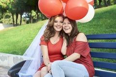 Δύο φίλοι που κάθονται στον πάγκο με τις σφαίρες στοκ εικόνες