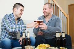 Δύο φίλοι που πίνουν την μπύρα στο σπίτι στοκ εικόνα