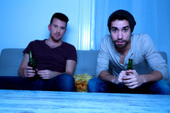 Δύο φίλοι που προσέχουν παθιασμένα τη TV με την μπύρα και τα τσιπ Στοκ Φωτογραφίες