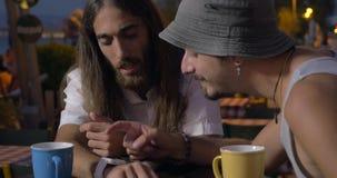 Δύο φίλοι που χρησιμοποιούν smartwatch στον καφέ οδών φιλμ μικρού μήκους