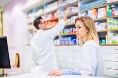 Δύο φαρμακοποιοί που εργάζονται σε ένα φαρμακείο στοκ εικόνες