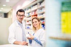 Δύο φαρμακοποιοί που εργάζονται σε ένα φαρμακείο στοκ εικόνα