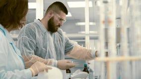 Δύο φαρμακοποιοί που προετοιμάζουν τον εξοπλισμό για τη δοκιμή στο εργαστήριο απόθεμα βίντεο