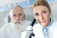 Δύο φαρμακοποιοί στα άσπρα παλτά που λειτουργούν με το μικροσκόπιο και που εξετάζουν τη κάμερα Στοκ Φωτογραφία