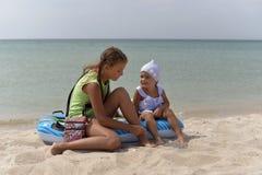 Δύο φιλικές αδελφές κοριτσιών χαλαρώνουν σε μια αμμώδη παραλία σε ένα καυτό καλοκαίρι στοκ εικόνα
