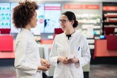 Δύο φιλικοί συνάδελφοι που μιλούν εργαζόμενοι μαζί ως φαρμακοποιοί στοκ φωτογραφία