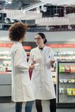 Δύο φιλικοί συνάδελφοι που μιλούν εργαζόμενοι μαζί ως φαρμακοποιοί στοκ φωτογραφίες