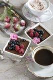 Δύο φλιτζάνια του καφέ, επιδόρπια σοκολάτας και φράουλες, εκλεκτής ποιότητας μαχαιροπήρουνα στοκ εικόνα