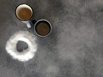 Δύο φλιτζάνια του καφέ και η αγάπη της ζάχαρης στοκ εικόνες