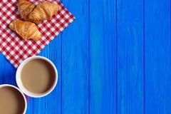 Δύο φλιτζάνια του καφέ και croissants στον μπλε ξύλινο πίνακα Στοκ φωτογραφία με δικαίωμα ελεύθερης χρήσης