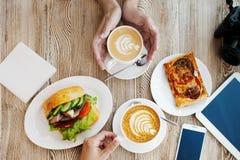 Δύο φλιτζάνια του καφέ, φιλική ατμόσφαιρα Σάντουιτς, φλιτζάνι του καφέ και smartphone κοτόπουλου στον πίνακα Στοκ Εικόνα