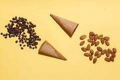 Δύο φλυτζάνια βαφλών, διεσπαρμένα φασόλια καφέ και αμύγδαλα στον κίτρινο καφετή πίνακα Το δημιουργικό επίπεδο βάζει το πρότυπο Στοκ Φωτογραφία