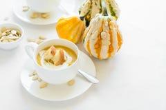 Δύο φλυτζάνια με τη φρέσκια κολοκύθας κρέμα, τους σπόρους και τις κροτίδες κρέμας διακοσμημένη σούπα Στοκ εικόνα με δικαίωμα ελεύθερης χρήσης