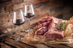 Δύο φλυτζάνια με το κόκκινο κρασί και την ακατέργαστη μπριζόλα βόειου κρέατος στον ξύλινο πίνακα στοκ φωτογραφίες