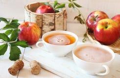Δύο φλυτζάνια του μηλίτη της Apple και των κόκκινων μήλων στο ξύλινο καλάθι Στοκ εικόνες με δικαίωμα ελεύθερης χρήσης