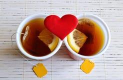 Δύο φλυτζάνια του τσαγιού με το λεμόνι και μιας καρδιάς φιαγμένης από ύφασμα στοκ εικόνες