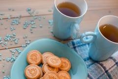 Δύο φλυτζάνια του τσαγιού σε μια μπλε πετσέτα Μπισκότα σε ένα μπλε πιάτο σε ένα ξύλινο υπόβαθρο Στοκ Φωτογραφία