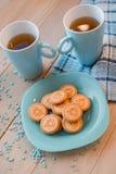 Δύο φλυτζάνια του τσαγιού σε μια μπλε πετσέτα Μπισκότα σε ένα μπλε πιάτο σε ένα ξύλινο υπόβαθρο Στοκ Εικόνες
